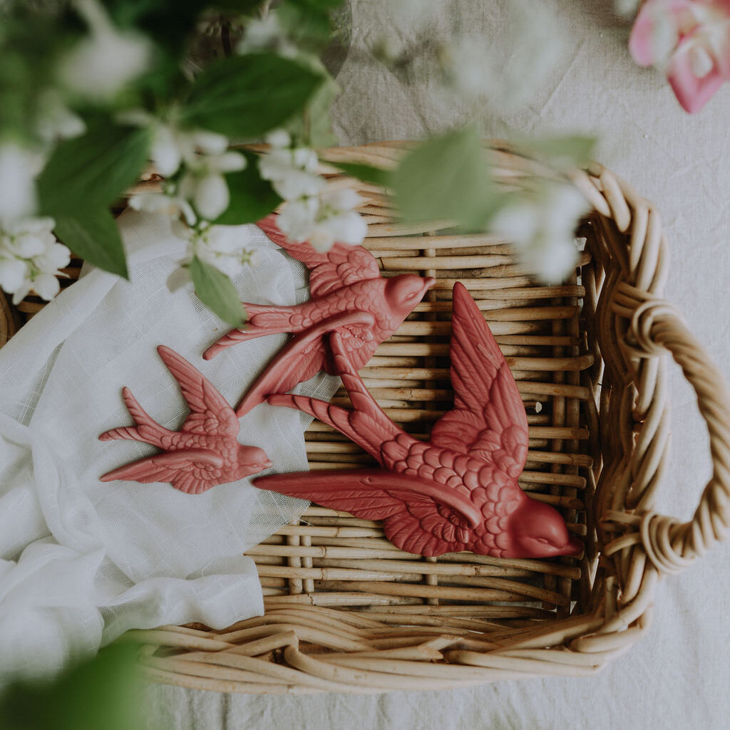 rosa svalor i keramik i en korg med blommor