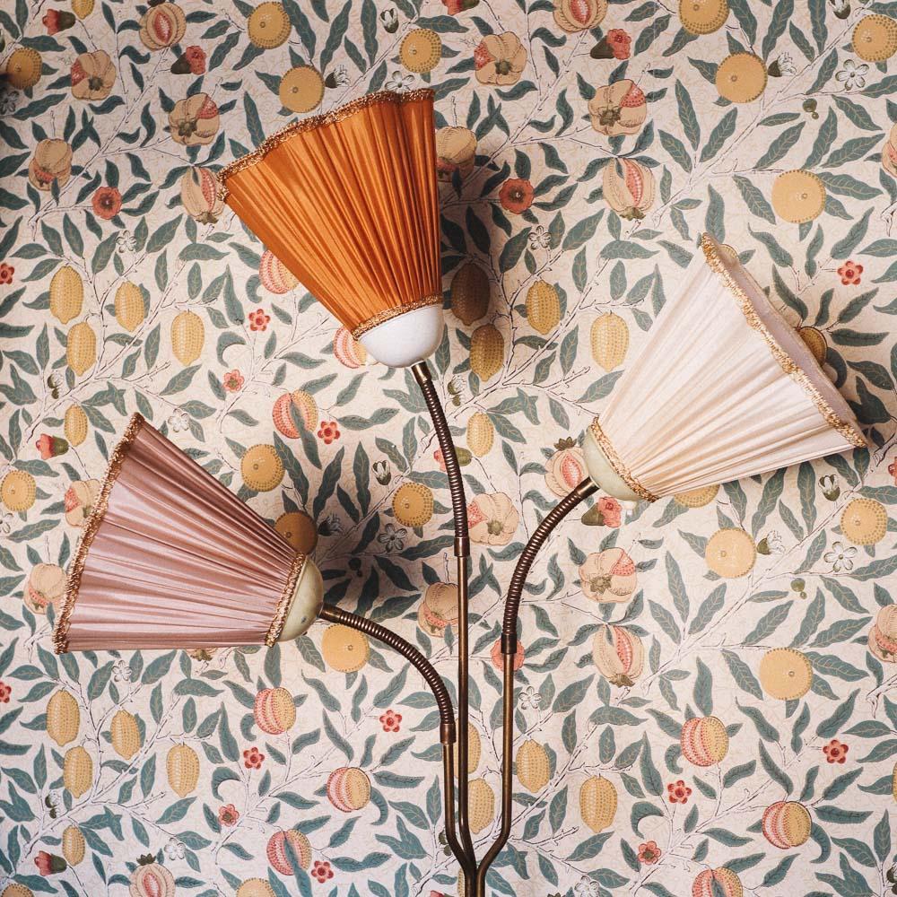 lampskarmar i olika farger med blommig tapet