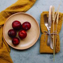 senapsgul bomullsservett med plommon och vintageporslin