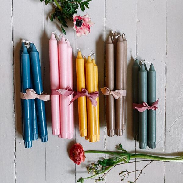 stearinljus i rosa, gult, blått och grönt med en blomma