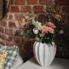 vit vas med blommor mot tegelvagg