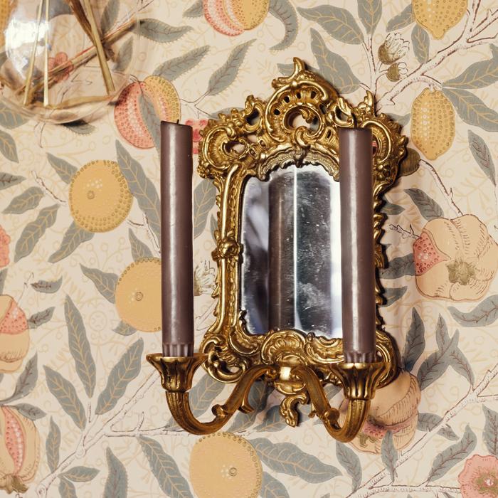 lampett massing med spegel mot blommig tapet
