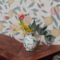 liten kanna med en blomma