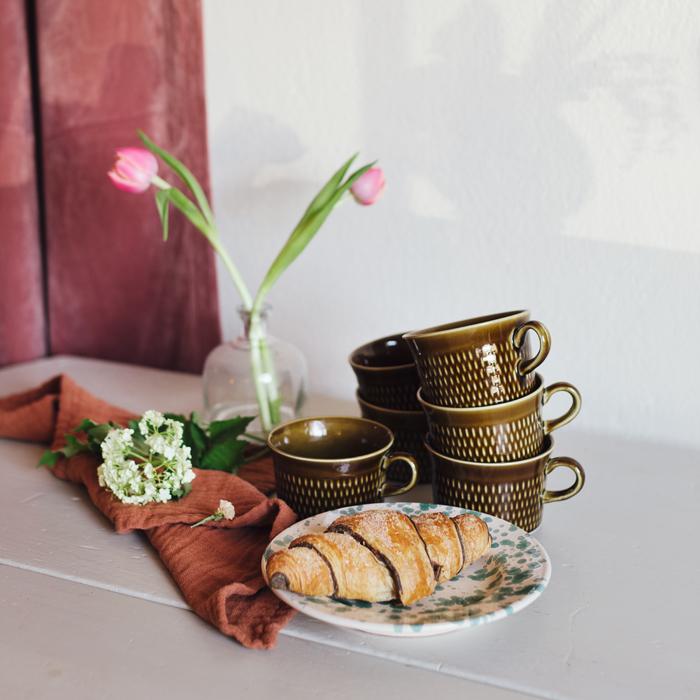 bruna koppar med fat och en pain au chocolat
