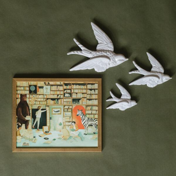 tavla med barn i bibliotek och svalor i keramik